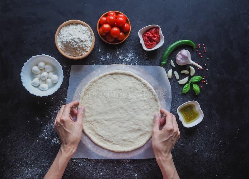 Κατασκευή της ζύμης από τα θηλυκά χέρια στο αρτοποιείο Κατασκευή της ιταλικής πίτσας Μαργαρίτα στοκ εικόνα με δικαίωμα ελεύθερης χρήσης