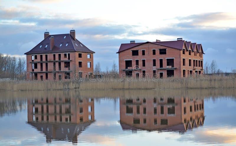 Κατασκευή των εξοχικών σπιτιών διαμερισμάτων από έναν τούβλινο στην όχθη ποταμού στοκ φωτογραφία