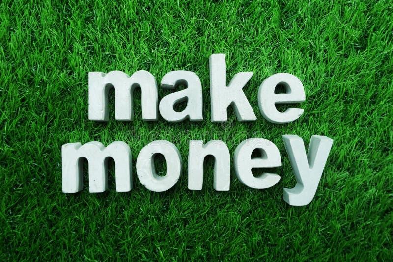 Καταστήστε τα χρήματα γίνοντα από το συγκεκριμένο αλφάβητο στην πράσινη χλόη στοκ φωτογραφίες με δικαίωμα ελεύθερης χρήσης