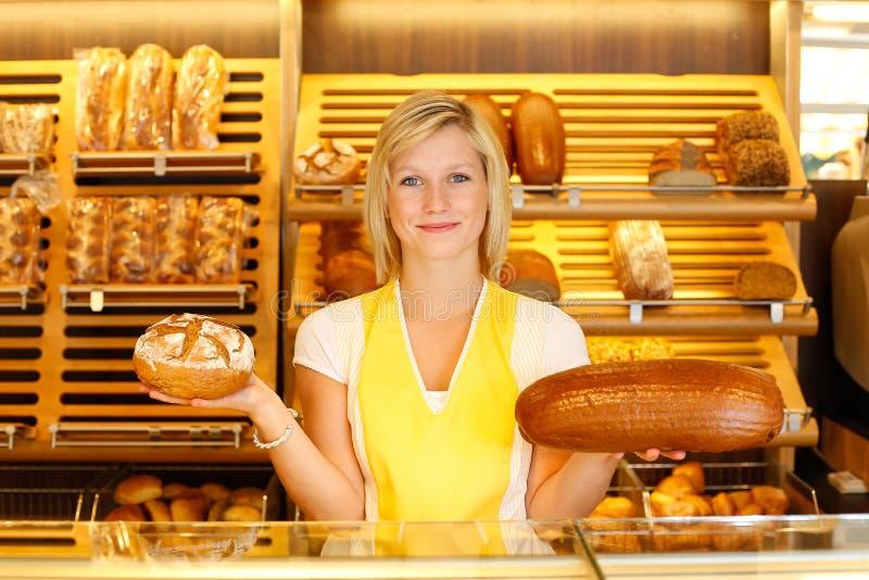 Καταστηματάρχης αρτοποιείων με δύο φραντζόλες του ψωμιού στοκ εικόνα