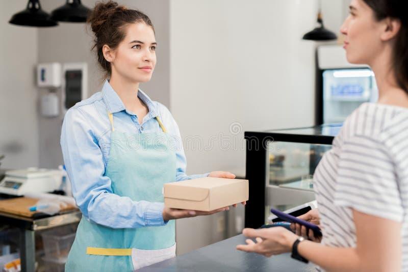 Καταστηματάρχης που δίνει το κιβώτιο στον πελάτη στοκ φωτογραφία