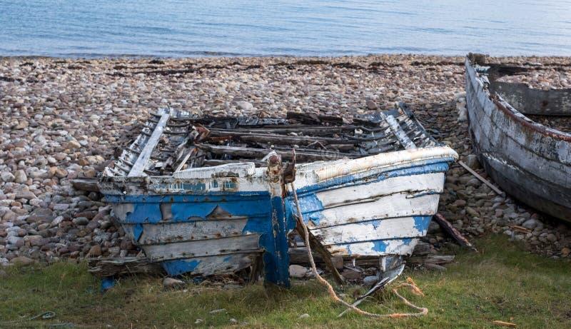 Καταστροφές της μικρής βάρκας στην παραλία σε Polbain, βόρεια Ullapool Στο υπόβαθρο, άποψη των θερινών νησιών, Σκωτία στοκ εικόνα