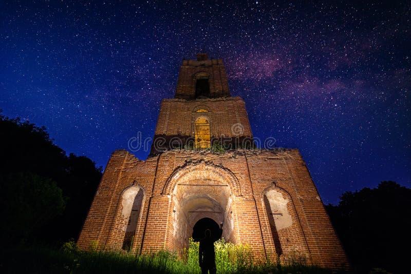 Καταστροφή πύργων κουδουνιών νύχτας στο δάσος στην έναστρη νύχτα και άτομο με το φακό κάτω από το στοκ φωτογραφία με δικαίωμα ελεύθερης χρήσης