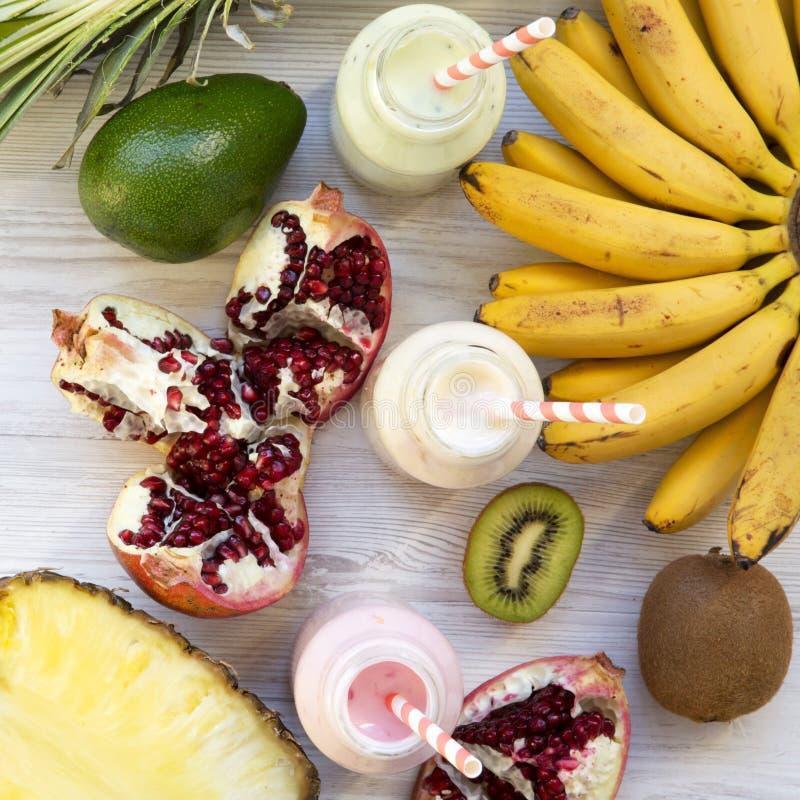 Καταφερτζήδες φρούτων ή milkshakes των διαφορετικών γούστων στα μπουκάλια γυαλιού με τα συστατικά στην άσπρη ξύλινη επιφάνεια, το στοκ φωτογραφία με δικαίωμα ελεύθερης χρήσης