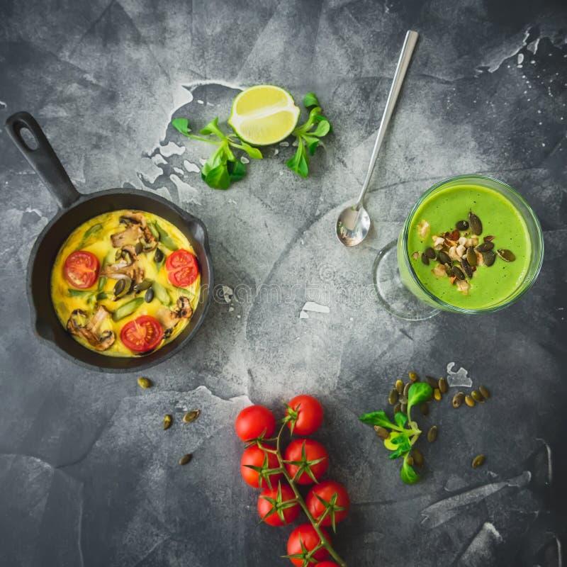 Καταφερτζής με το σπανάκι, τους χορτοφάγους σπόρους ομελετών, ντοματών και κολοκύθας Επίπεδος βάλτε, τοπ άποψη Πλαίσιο τροφίμων στοκ εικόνες με δικαίωμα ελεύθερης χρήσης