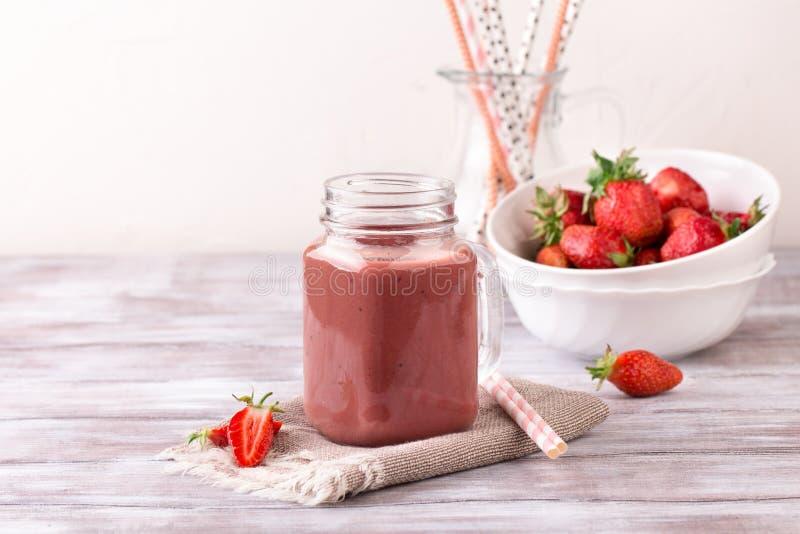 Καταφερτζής φραουλών ή milkshake στο βάζο στο άσπρο ξύλινο αγροτικό υπόβαθρο στοκ εικόνες