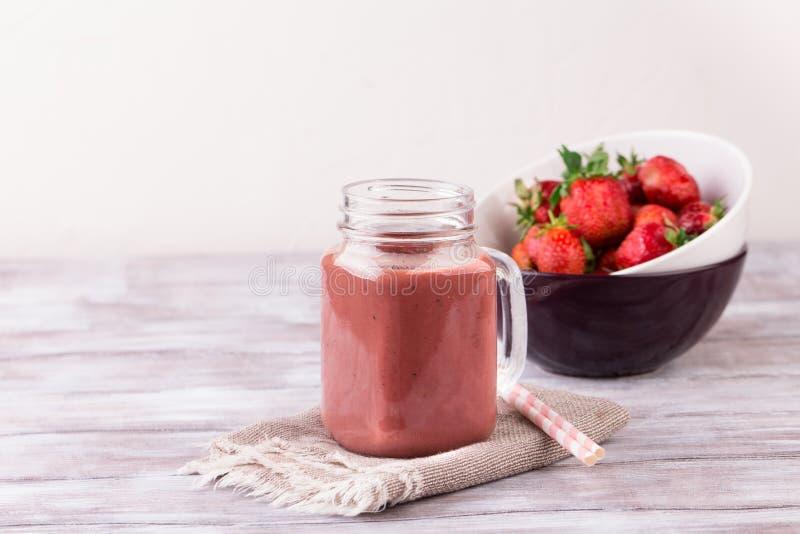 Καταφερτζής φραουλών ή milkshake στο βάζο στο άσπρο ξύλινο αγροτικό υπόβαθρο στοκ εικόνες με δικαίωμα ελεύθερης χρήσης