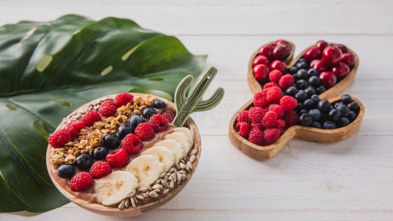 Καταφερτζής Acai, granola, σπόροι, νωποί καρποί σε ένα ξύλινο κύπελλο με το κουτάλι κάκτων Πιάτο που γεμίζουν με τα μούρα στο λευ στοκ φωτογραφία