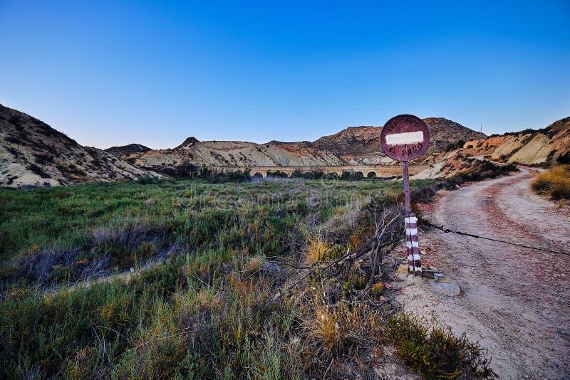 """Κατευθύνσεις των σημαδιών """"που απαγορεύονται """"στο δρόμο που οδηγεί στο παλαιό υδραγωγείο στα βουνά κοντά BIC δ στη """"Elx εσωρούχων στοκ φωτογραφίες με δικαίωμα ελεύθερης χρήσης"""