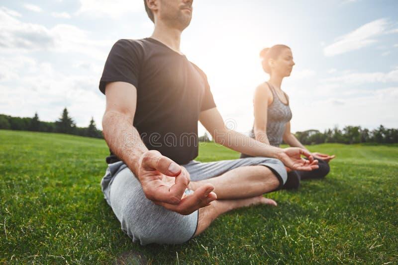 Κατηγορία γιόγκας Το νέο ζεύγος και κάνοντας τις ασκήσεις γιόγκας καθμένος στο λωτό θέστε σε μια πράσινη χλόη σε ανοικτό στοκ φωτογραφία