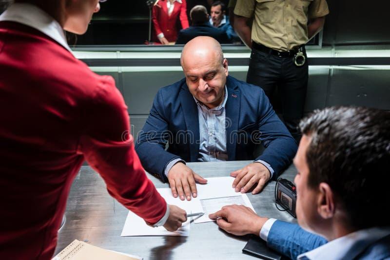 Κατηγορούμενος ή μάρτυρας που δέχεται συμβουλές από το δικηγόρο για να υπογράψει μια επίσημη ανακοίνωση στοκ φωτογραφία
