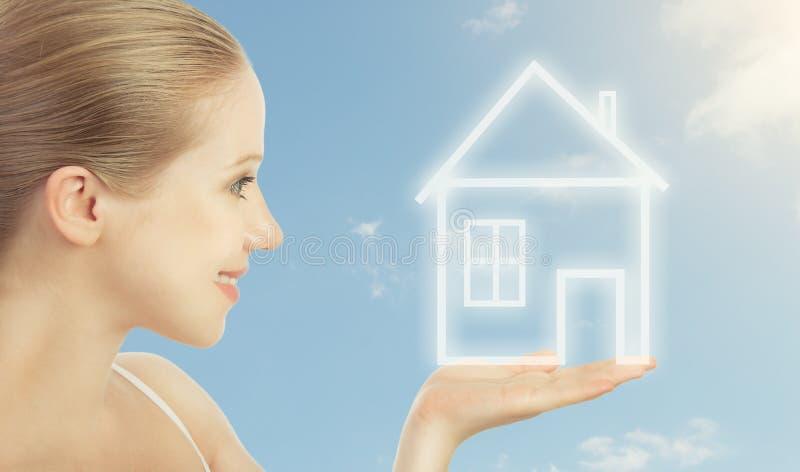 Κατοικία έννοιας. γυναίκα που κρατά ένα σπίτι στοκ εικόνες