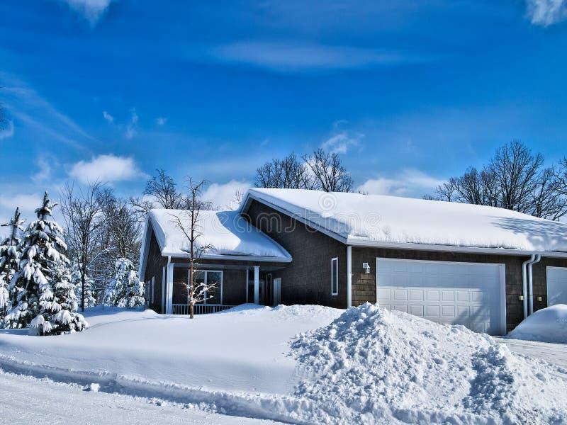 Κατοικημένο σπίτι με το χιόνι στη στέγη το χειμώνα στοκ εικόνες με δικαίωμα ελεύθερης χρήσης