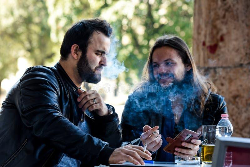 Κατοχή ενός καπνού με μια μπύρα που ελέγχει έξω κάτι στο διαδίκτυο στοκ φωτογραφία με δικαίωμα ελεύθερης χρήσης