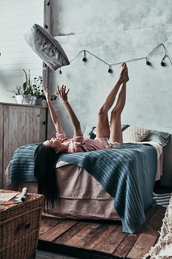 Κατοχή της διασκέδασης! Ελκυστική νέα γυναίκα που ρίχνει επάνω σε ένα μαξιλάρι και smil στοκ εικόνες