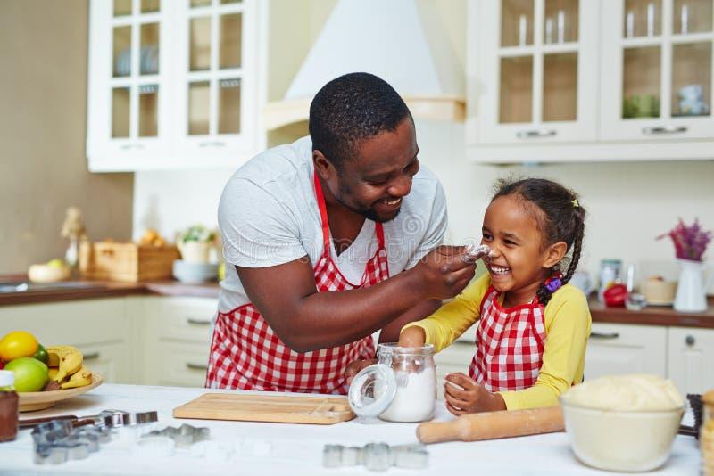 Κατοχή της διασκέδασης κατά τη διάρκεια του μαγειρέματος στοκ φωτογραφία