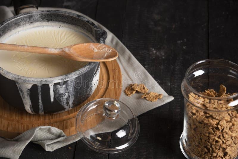 Κατσαρόλλα με το γάλα και ένα βάζο με τα δημητριακά στοκ φωτογραφίες
