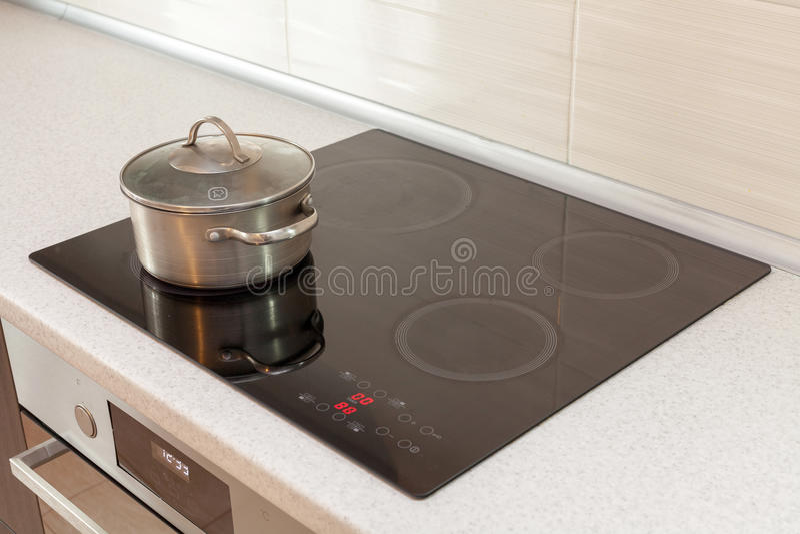 Κατσαρόλλα χάλυβα μετάλλων στη σύγχρονη κουζίνα με τη σόμπα επαγωγής στοκ φωτογραφία με δικαίωμα ελεύθερης χρήσης