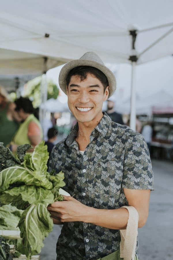 Κατσαρό λάχανο αγοράς ατόμων σε μια αγορά αγροτών στοκ εικόνες