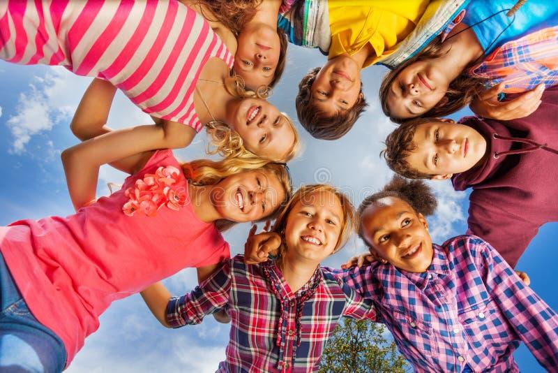 Κατώτατη άποψη της ομάδας παιδιών που στέκεται στη στρογγυλή μορφή στοκ φωτογραφία
