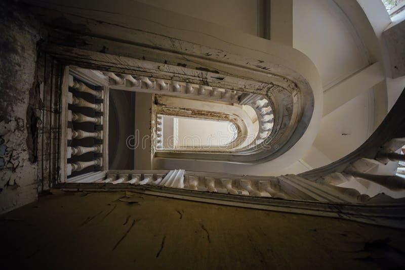 Κατώτατη άποψη της παλαιάς εκλεκτής ποιότητας διακοσμημένης σκάλας στο εγκαταλειμμένο μέγαρο στοκ εικόνες με δικαίωμα ελεύθερης χρήσης