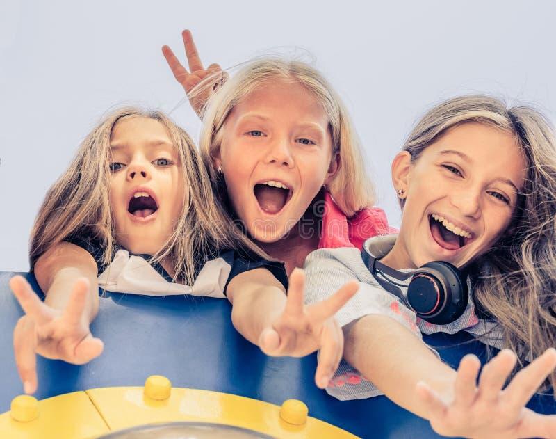 Κατώτατη άποψη των όμορφων χαμογελώντας μικρών κοριτσιών που στέκονται από κοινού στοκ φωτογραφίες