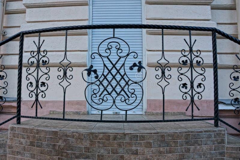 Κατώτατο όριο με έναν διακοσμητικό φράκτη σιδήρου με τις ράβδους με ένα σφυρηλατημένο σχέδιο κοντά στον τοίχο στοκ εικόνες