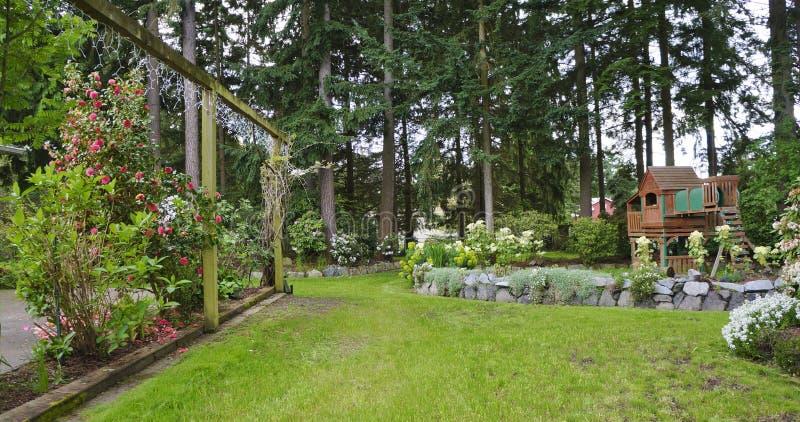 Κατώφλι άνοιξη σπιτιών με το patio τριαντάφυλλων και την παιδική χαρά παιδιών. στοκ εικόνες