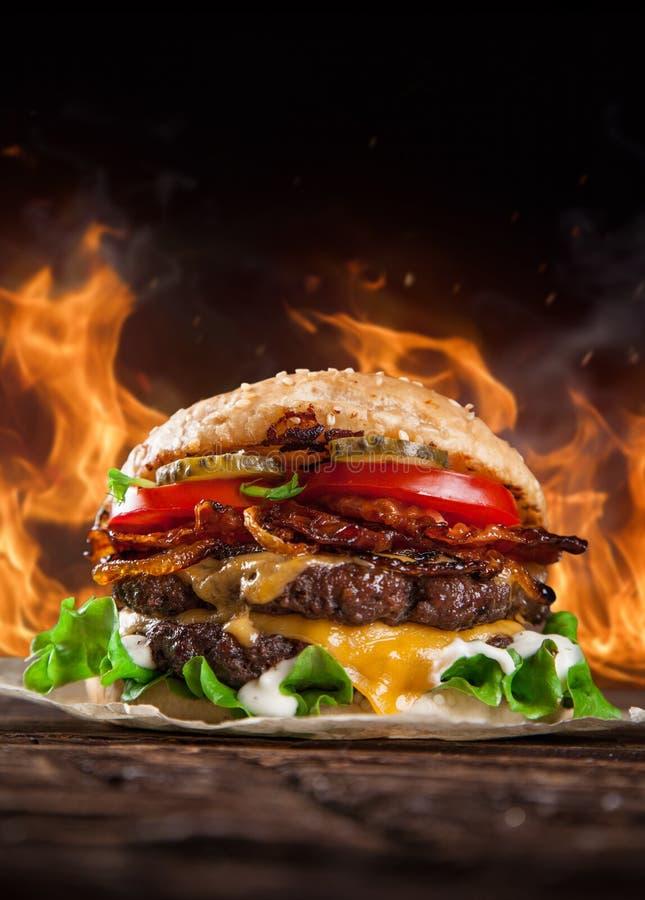Κατ' οίκον γίνοντα burgers με τις φλόγες πυρκαγιάς στοκ φωτογραφίες με δικαίωμα ελεύθερης χρήσης