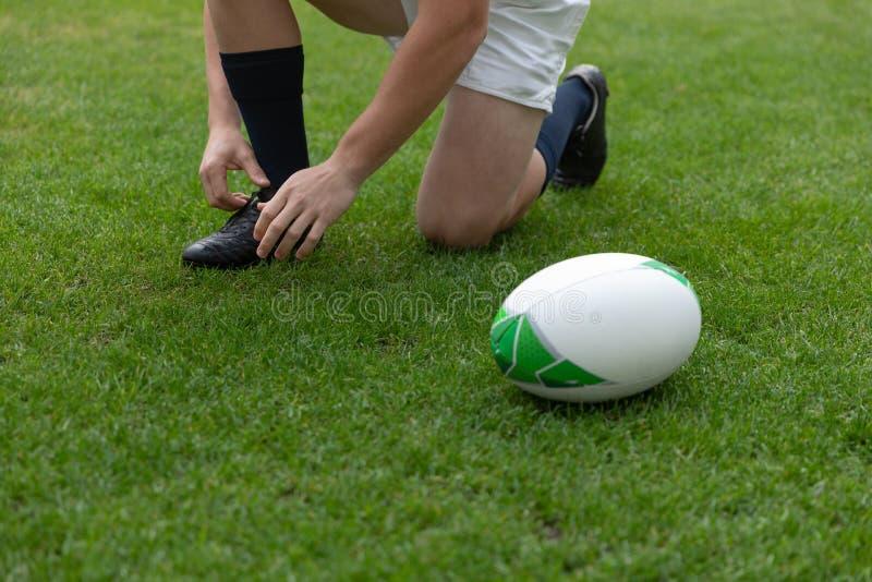 Καυκάσια αρσενικά δένοντας κορδόνια φορέων ράγκμπι στο στάδιο στοκ φωτογραφία
