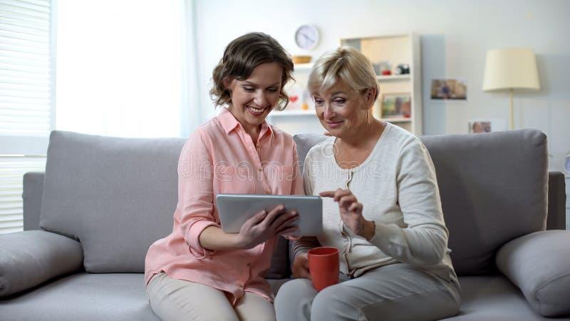 Καυκάσια γυναίκα με την ηλικιωμένη μητέρα που χρησιμοποιεί την ταμπλέτα, εύκολη εφαρμογή πληρωμής στοκ φωτογραφία με δικαίωμα ελεύθερης χρήσης