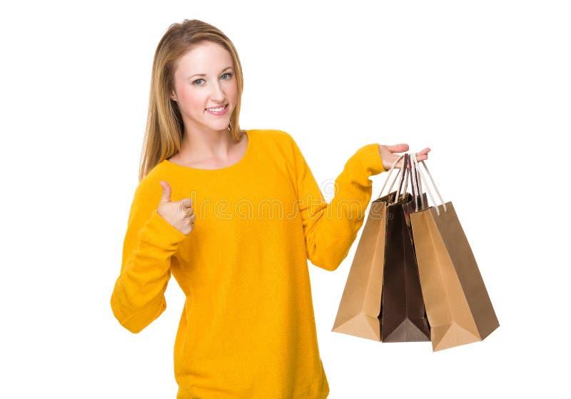 Καυκάσια γυναίκα με την τσάντα και τον αντίχειρα αγορών επάνω στοκ εικόνες