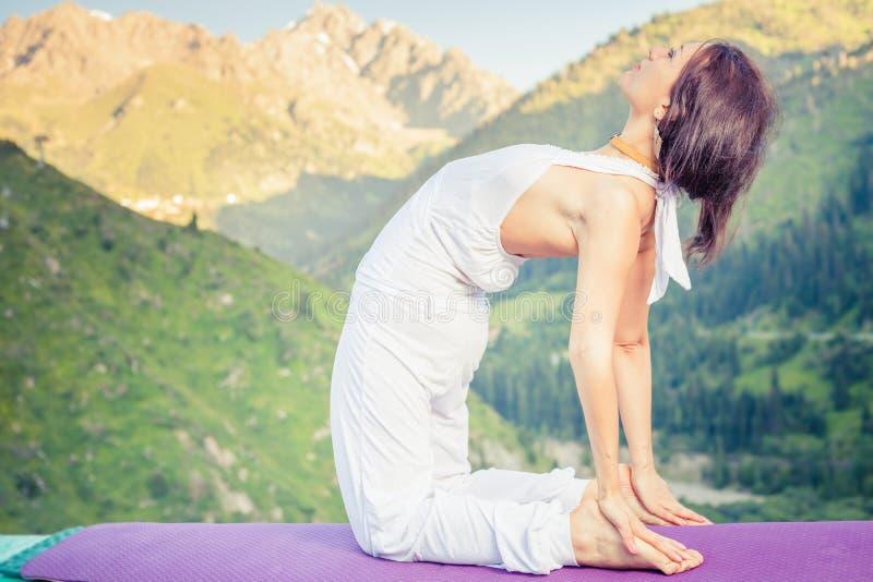 Καυκάσια γυναίκα που κάνει τη γιόγκα στο βουνό στοκ εικόνες