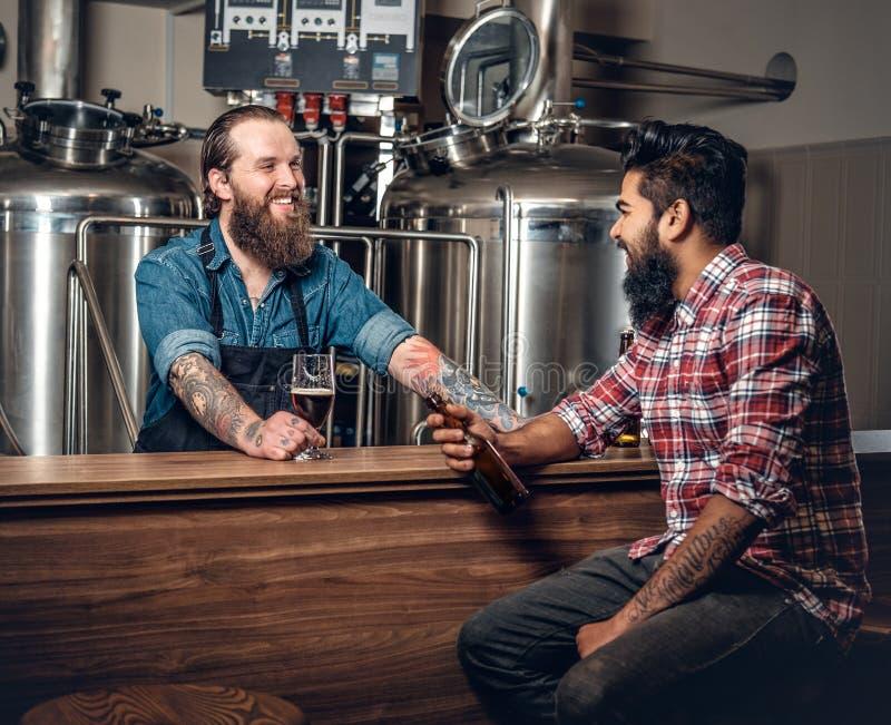 Καυκάσια και ινδικά άτομα που παρουσιάζουν την μπύρα τεχνών στο microbrewery στοκ φωτογραφία