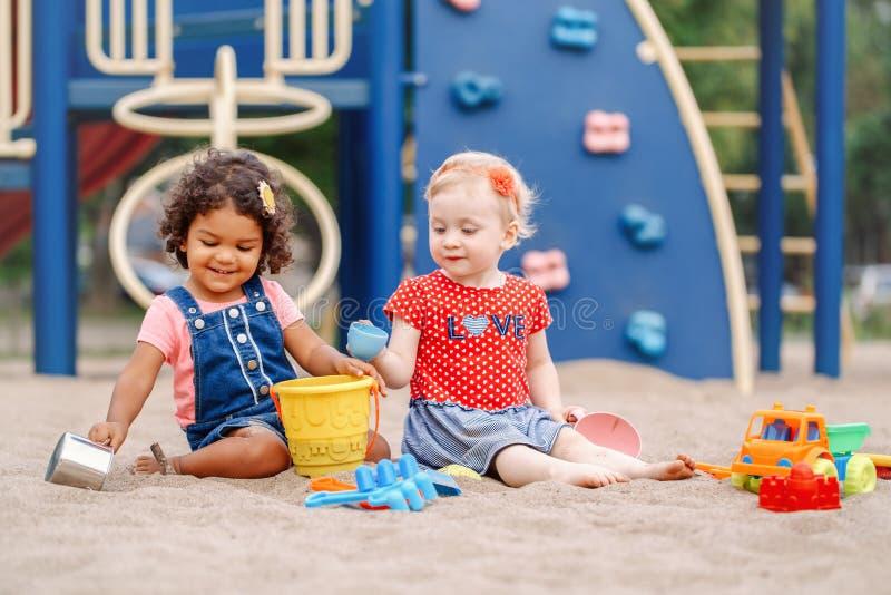 Καυκάσια και ισπανικά λατινικά παιδιά μωρών που κάθονται στο παιχνίδι Sandbox στοκ εικόνα με δικαίωμα ελεύθερης χρήσης