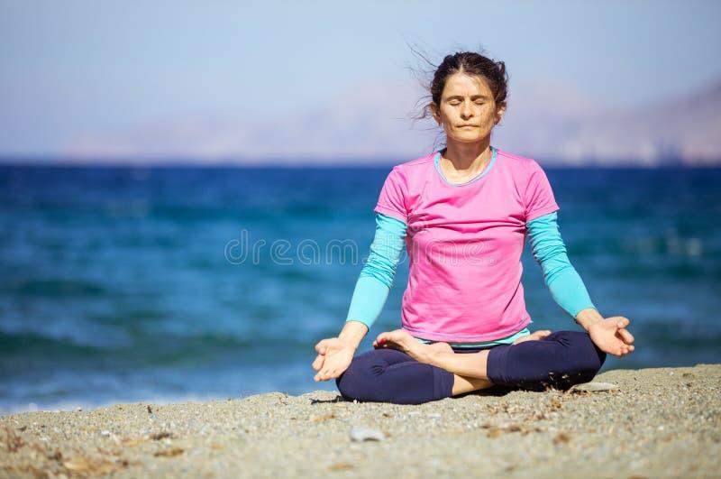 Καυκάσια νέα γιόγκα άσκησης γυναικών στην παραλία στοκ φωτογραφία