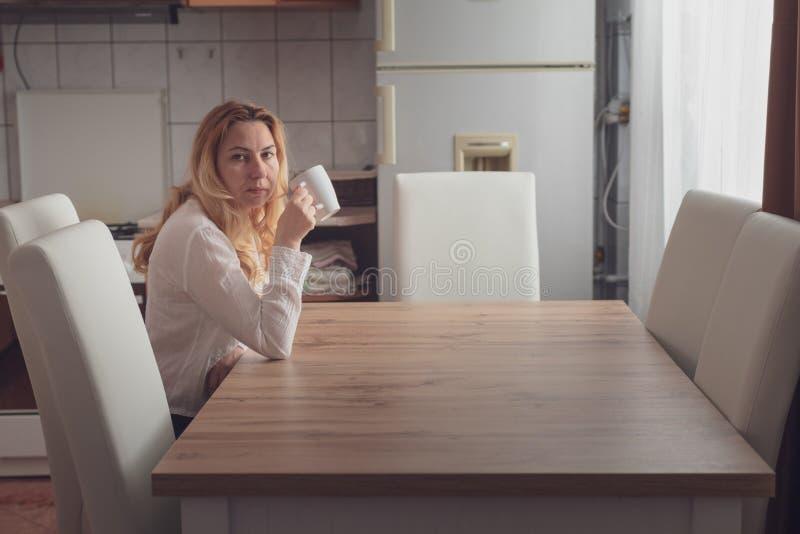 Καυκάσια ξανθή συνεδρίαση γυναικών στον πίνακα κουζινών κατά τη διάρκεια του πρωινού και της κατανάλωσης ενός καυτού φλιτζανιού τ στοκ εικόνες