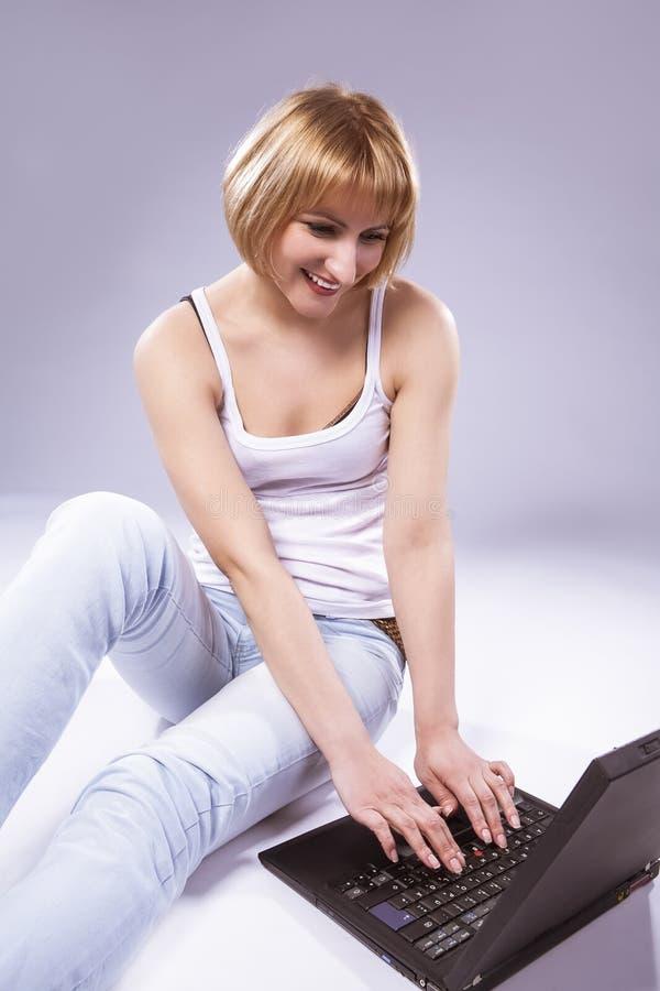 Καυκάσια ξανθή τοποθέτηση γυναικών Tranqiul με το lap-top στοκ φωτογραφία με δικαίωμα ελεύθερης χρήσης