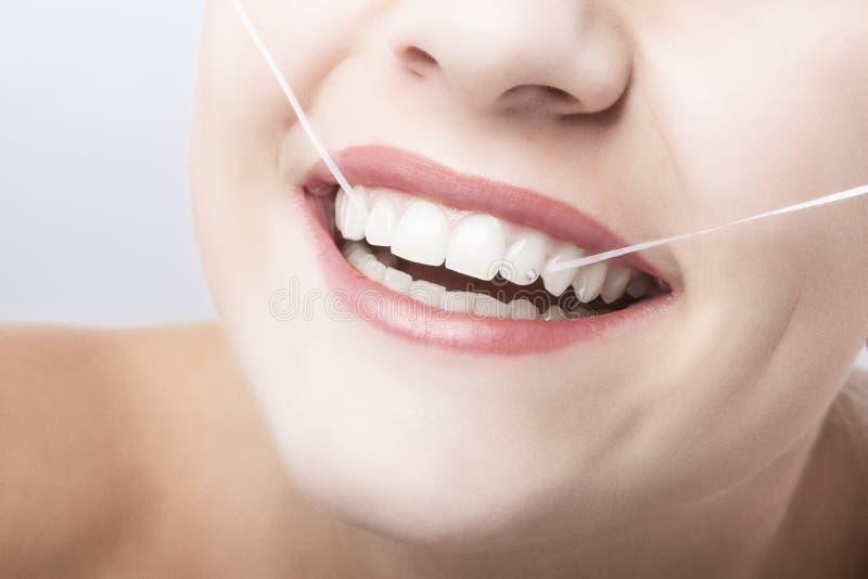 Καυκάσια στοματική κινηματογράφηση σε πρώτο πλάνο γυναικών με το οδοντικό νήμα. στοκ φωτογραφία με δικαίωμα ελεύθερης χρήσης