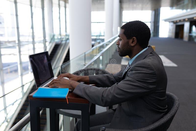 Καυκάσια συνεδρίαση επιχειρηματιών στον πίνακα και εργασία στο lap-top στο σύγχρονο γραφείο στοκ εικόνα με δικαίωμα ελεύθερης χρήσης