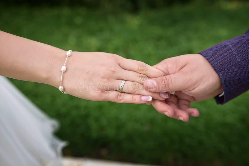 Καυκάσια χέρια εκμετάλλευσης ζευγών, νυφών και νεόνυμφων με την ορατά δέσμευση και τα γαμήλια δαχτυλίδια, με θολωμένο, υπόβαθρο έ στοκ φωτογραφία με δικαίωμα ελεύθερης χρήσης