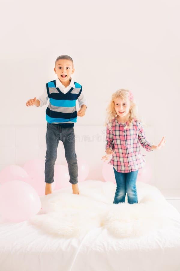 Καυκάσια χαριτωμένα λατρευτά αστεία παιδιά που πηδούν στο κρεβάτι στοκ εικόνες
