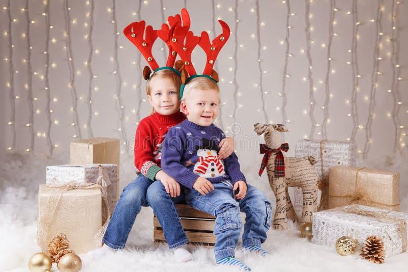 Καυκάσιοι αδελφός και αδελφή παιδιών στα πουλόβερ που κάθονται μαζί να αγκαλιάσει τα Χριστούγεννα εορτασμού ή το νέο έτος στοκ φωτογραφίες