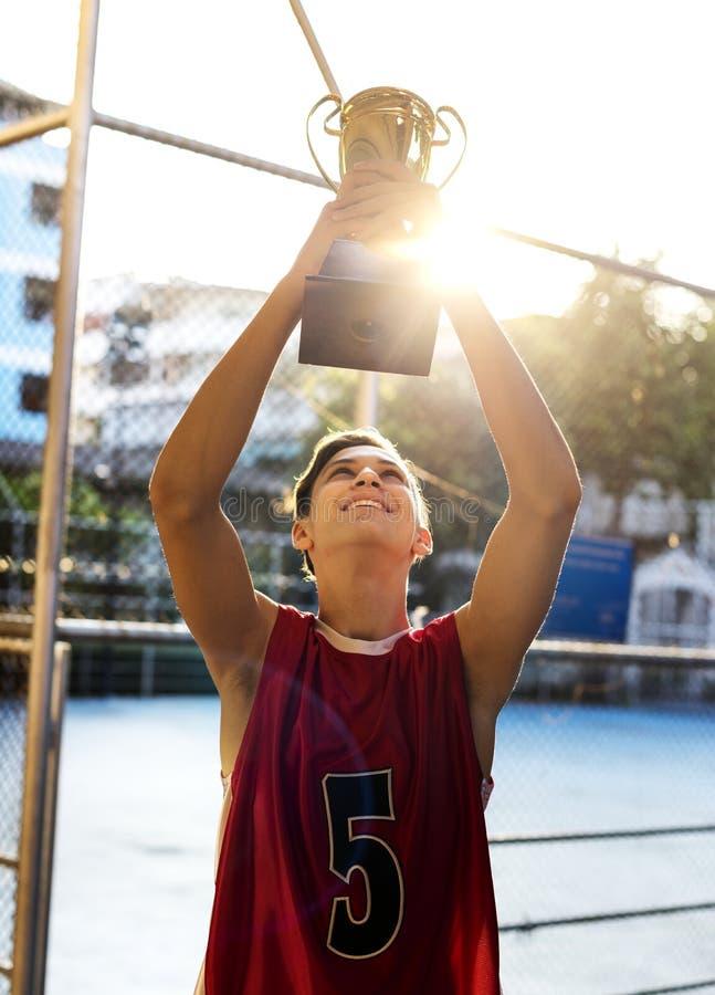 Καυκάσιος έφηβος στα φίλαθλα ενδύματα που κρατούν ψηλά ένα τρόπαιο υπαίθρια στοκ φωτογραφία