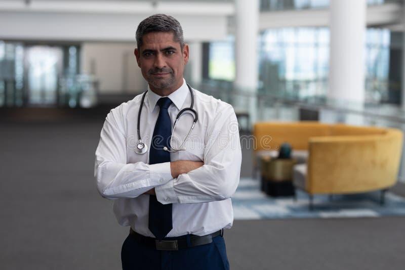Καυκάσιος αρσενικός γιατρός με τα όπλα που διασχίζονται εξέταση τη κάμερα στην κλινική στοκ φωτογραφίες