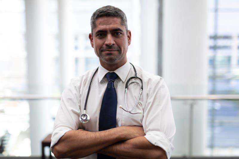 Καυκάσιος αρσενικός γιατρός με τα όπλα που διασχίζονται εξέταση τη κάμερα στην κλινική στοκ εικόνα με δικαίωμα ελεύθερης χρήσης
