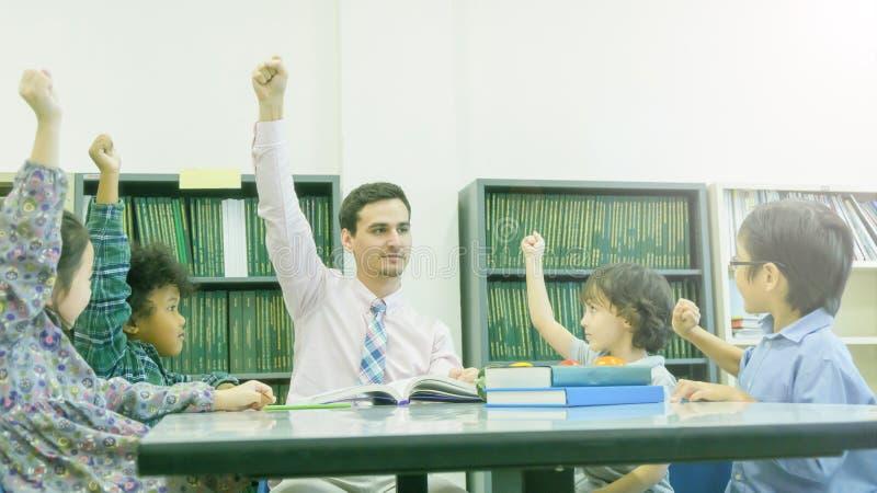 Καυκάσιος δάσκαλος Smiley και ομαδοποίηση του ασιατικού σπουδαστή παιδιών lear στοκ φωτογραφίες