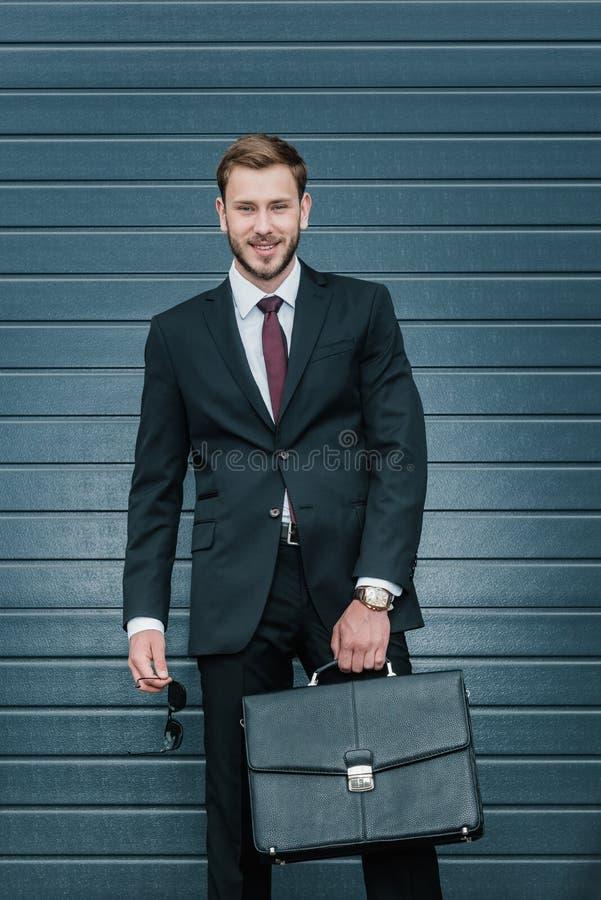 Καυκάσιος επιχειρηματίας που στέκεται στο μαύρο κοστούμι, που χαμογελά και που κρατά το χαρτοφύλακα στοκ φωτογραφίες με δικαίωμα ελεύθερης χρήσης
