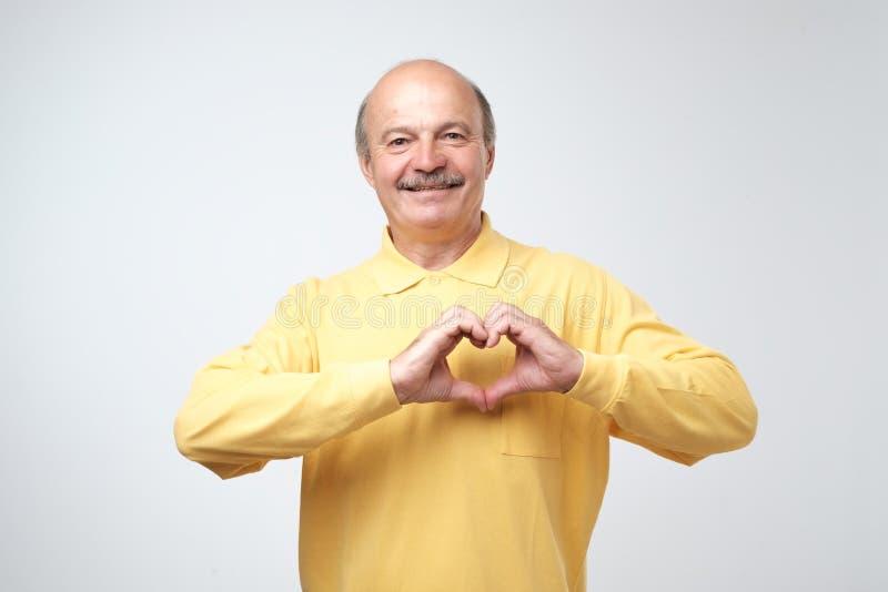 Καυκάσιος ηληκιωμένος στην κίτρινη μπλούζα που κάνει έξω της καρδιάς χεριών στοκ εικόνες με δικαίωμα ελεύθερης χρήσης