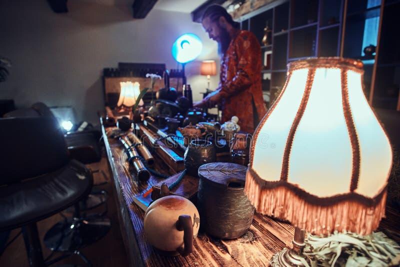 Καυκάσιος κύριος στο κιμονό που κατασκευάζει το φυσικό τσάι στο σκοτεινό δωμάτιο με ένα ξύλινο εσωτερικό Παράδοση, υγεία, αρμονία στοκ εικόνες